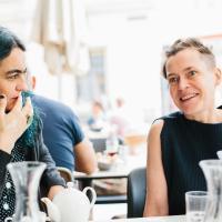 Susanne Kirchmayr aka Electric Indigo und Angélica Castelló im Interview. Sie sitzen an einem Tisch, Susanne Kirchmayr hat einen Sidecut, trägt ein schwarzes Oberteil und lacht. Susanne Kirchmayr hat schwarz-grüne Haare. Foto: Niko Havranek