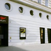 Fassade des Filmmuseums. Zu sehen ist die schwarze Eingangstür, einige Filmposter und runde Fenster