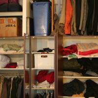 Ein begehbarer Kleiderschrank, voll mit unterschiedlicher Kleidung