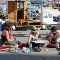 Foto von 3 malenden Personen, sitzend auf dem Boden in einem Hafen