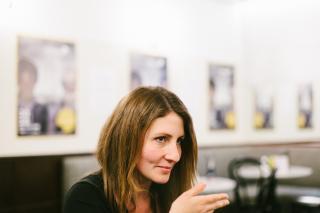 Regisseurin Jessica Bollag in einer Interviewsituation. Sie hebt die Hand und blickt konzentriert zu ihrer Interviewerein, die jedoch nicht im Bild ist.