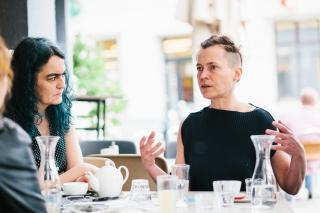 Angélica Castelló und  Susanne Kirchmayr aka Electric Indigo in einer Interviewsituation an einem Cafétisch im Freien.