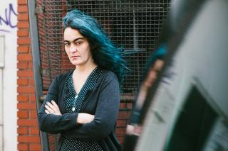 Angélica Castelló steht vor einer roten Ziegelsteinwand und einem Metallgitter. Sie hat lange lockige schwarz-grüne Haare die im Wind wehen, trägt dunkle Kleidung, hat die Arme verschränkt und schaut skeptisch.