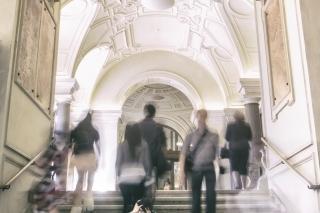 Foto einer Studentin in den Gängen der Universität Wien. Sie ist scharf zu sehen, alle anderen sind verschwommen. Es entsteht ein Eindruck von Orientierungslosigkeit