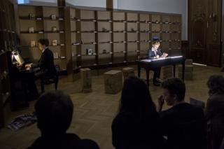 Theaterszene. Ein Mann sitzt am Klavier, eine Frau an einem beleuchteten Tisch, vor ihnen ist das Publikum zu sehen.