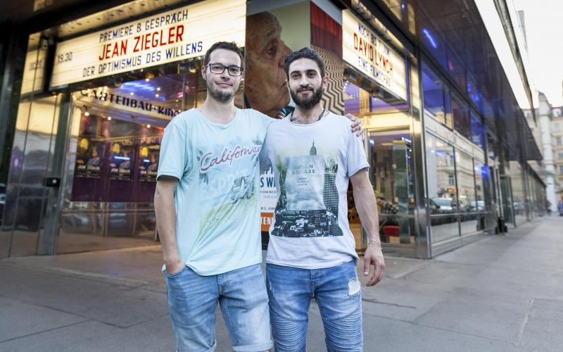 Zwei Junge Männer haben sich freundschaftlich im Arm und grinsen in die Kamera. Sie stehen vor einem Kino