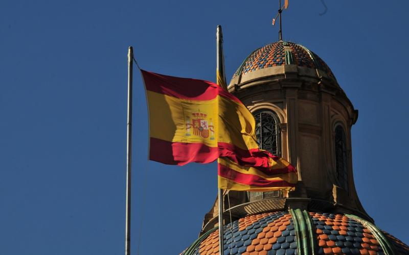 Foto einer im Wind wehenden, spanischen Flagge. Im Hintergrund eine Gebäudekuppel