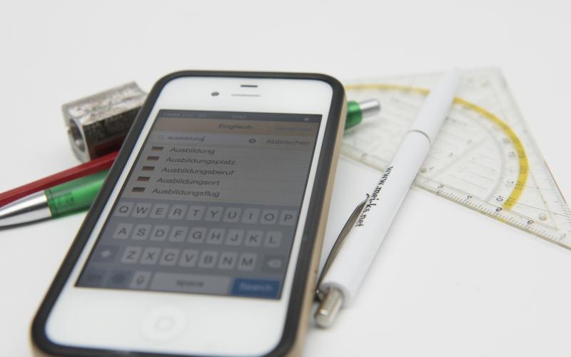 """Foto eines Smartphones, auf dem der Wörterbucheintrag für den Begriff """"Ausbildung"""" zu sehen ist. Das Smartphone liegt neben Stiften und einem Geodreieck"""