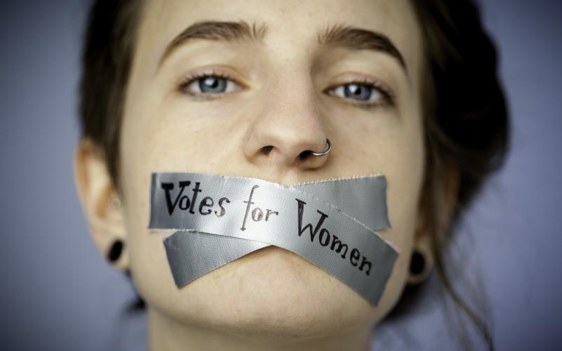 """Foto einer jungen Frau, deren Mund zugeklebt ist. Auf dem Klebeband steht """"Votes for Women"""" (Wahlrecht für Frauen)  Foto: Johanna Rauch"""