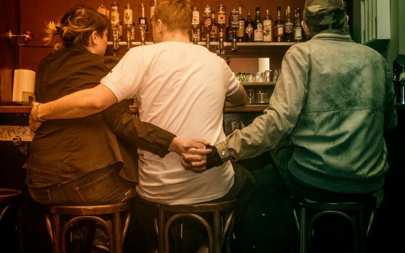 Foto von drei Menschen an einer Bar. Alle drei sitzen auf Barhockern, wir sehen nur ihre Rücken. Sie umarmen sich alle drei miteinander.