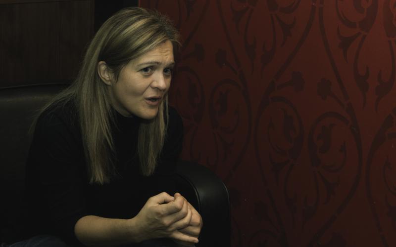 Foto von Barbara Eder in einem schwarzen Sessel vor einer roten, gemusterten Wand. Barbara Eder schaut konzentriert, Interviewsituation.