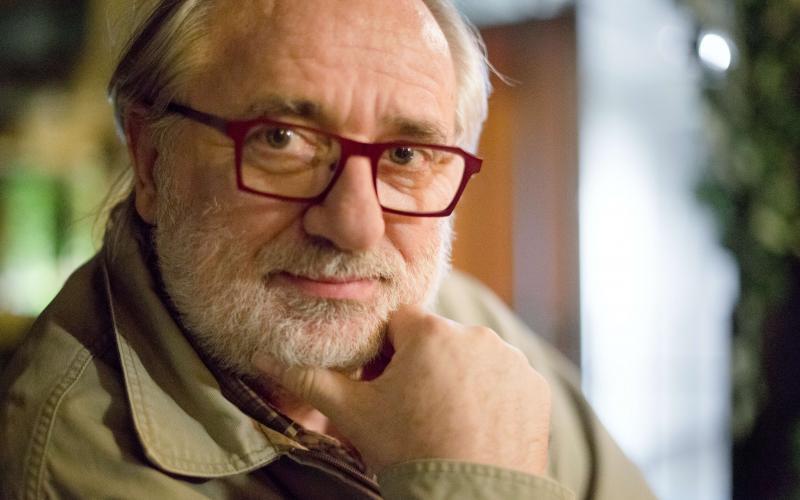 Ein Foto von Giorgos Chondors. Er schaut nachdenklich in die Kamera. Er trägt eine rote Brille und hat einen grauen, dünnen Vollbart.
