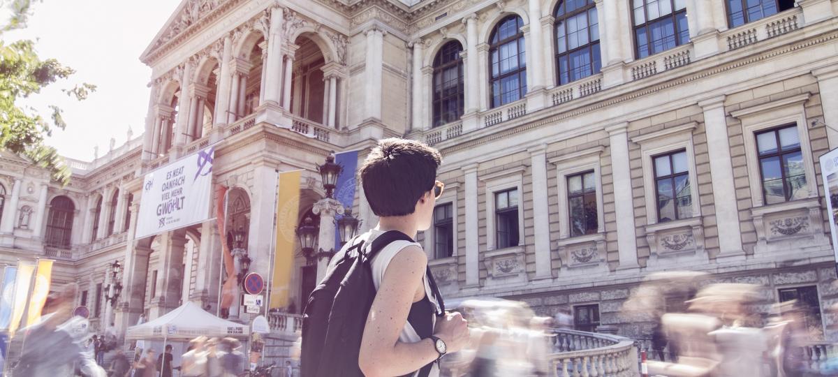 Foto einer Studentin vor der Universität Wien. Sie ist scharf zu sehen, alle anderen sind verschwommen. Es entsteht ein Eindruck von Orientierungslosigkeit
